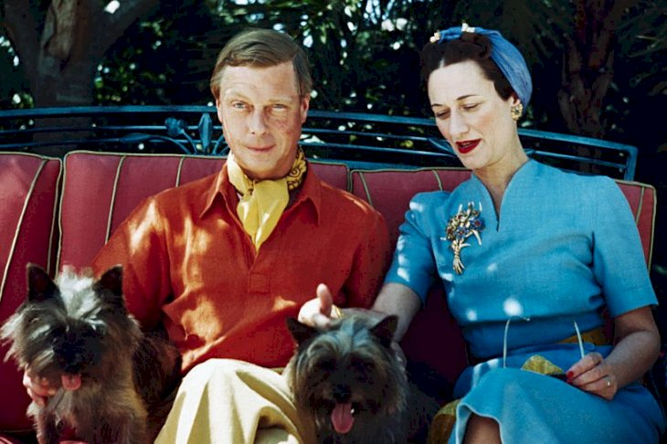 Image Credits: Getty Images / Bettmann | The Duke and Duchess of Windsor seated outdoors with two small dogs.