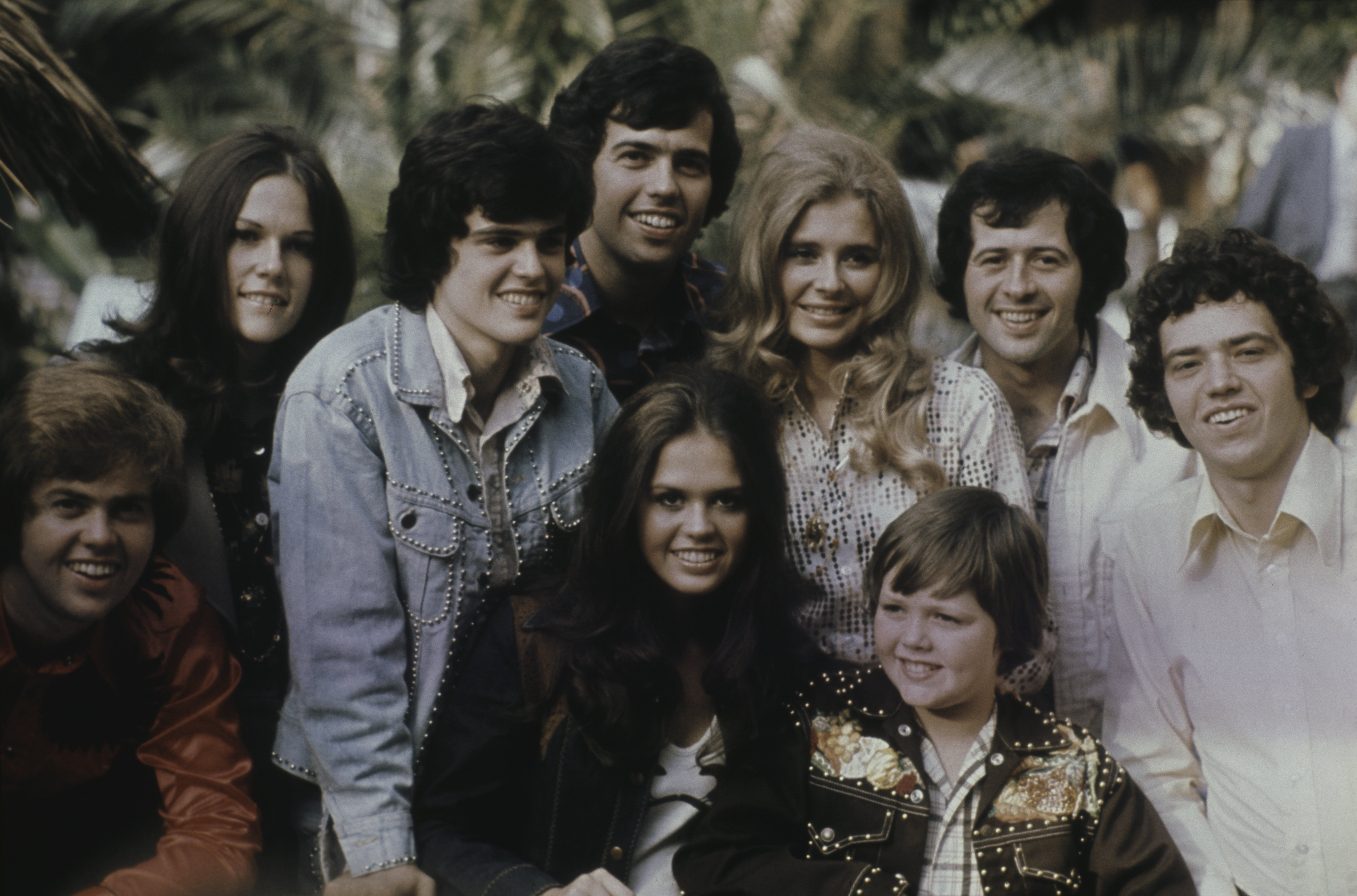 Image Credits: Getty Images / Michael Putland | Group portrait of American family vocal group The Osmonds posed with friends in 1973. Group members are, from left to right, Merrill Osmond, unknown woman, Donny Osmond, Alan Osmond, Marie Osmond, unknown woman, Jimmy Osmond (bottom) Wayne Osmond and unknown man.