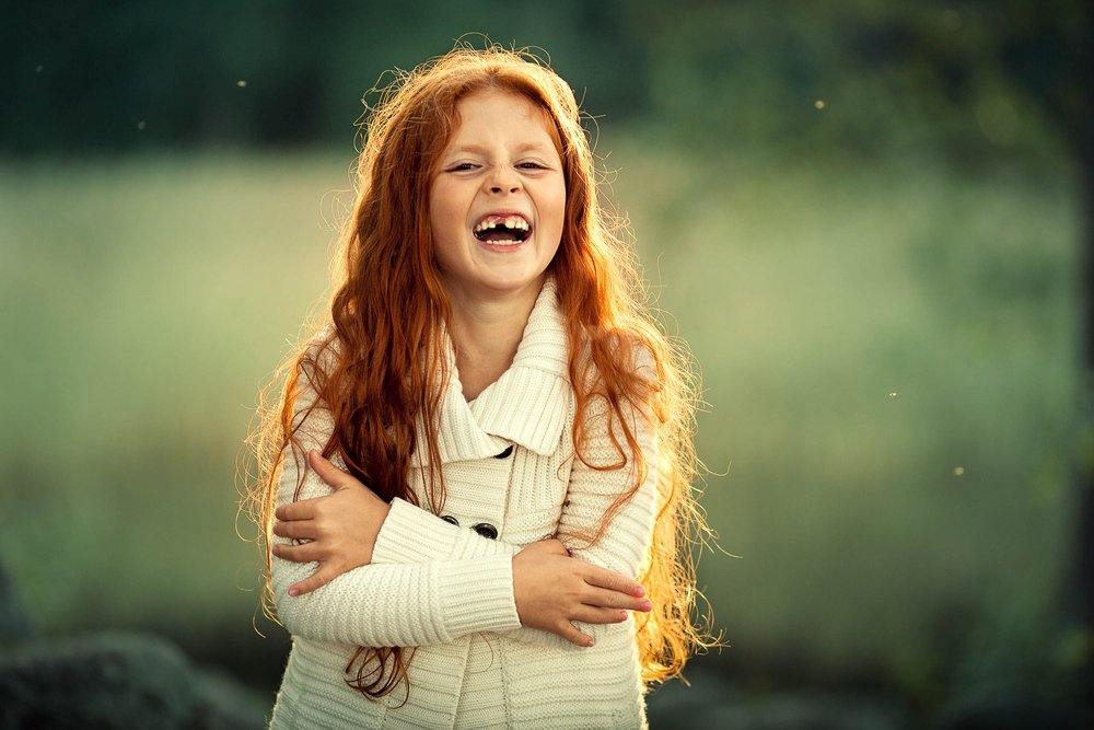Red haired girl laughing happily | Shutterstock