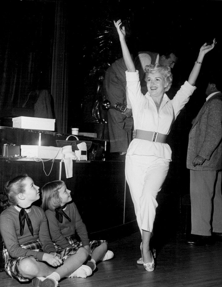 Image Source: Wikimedia Commons|Betty Grable's daughters Victoria and Elizabeth watch as their mother rehearses for the premiere of the television program A Shower of Stars