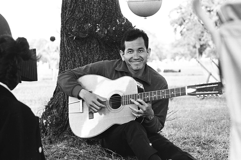 Image Credit: Getty Images / Trini Lopez is filmed sitting playing guitar in a London park, circa 1965.