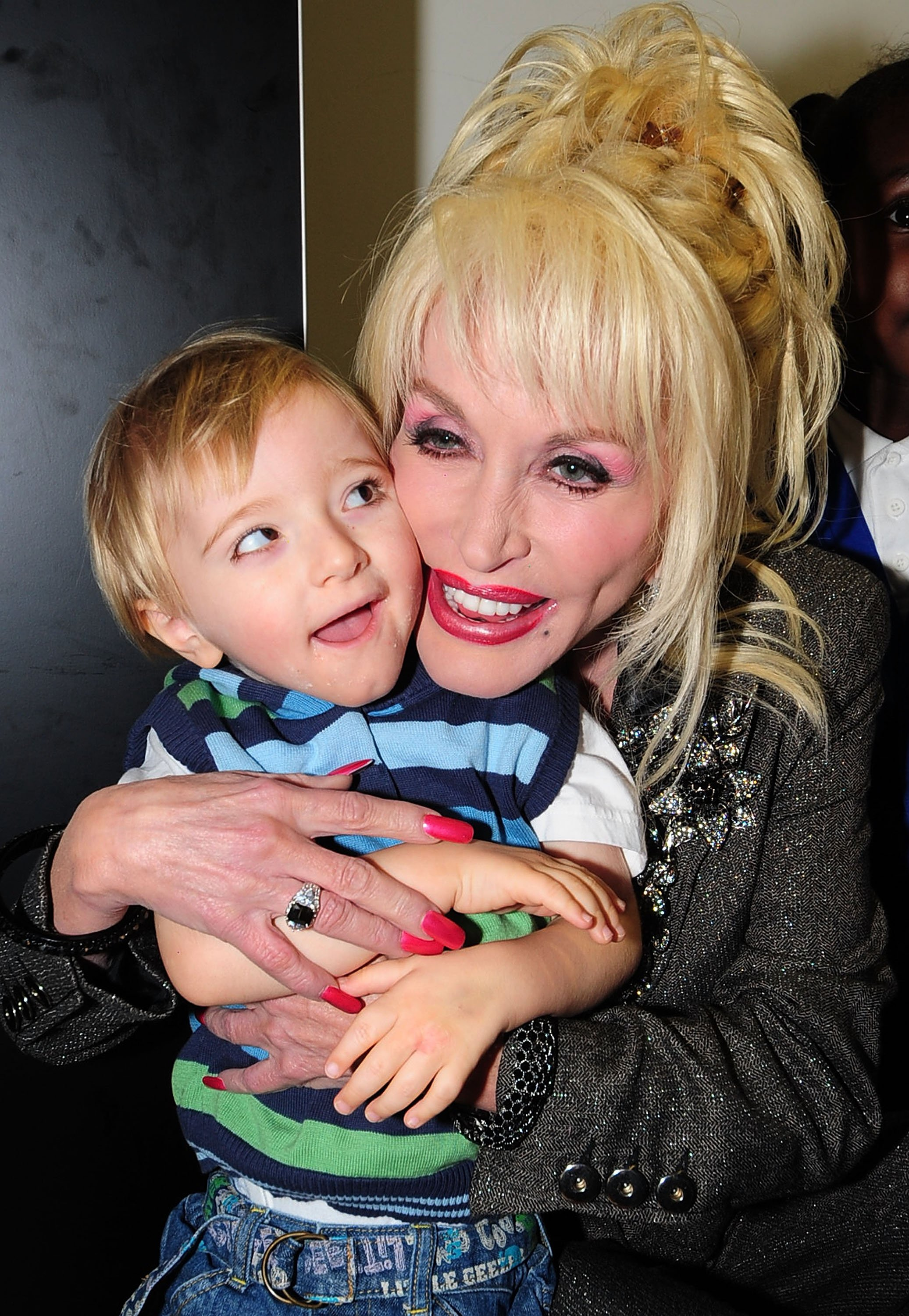 Image Credits: Getty Images / Pool | Country and western superstar singer Dolly Parton meets young children at the Magna Science And Adventure Park on December 5, 2007 in Rotherham, South Yorkshire, England. Dolly Parton honoured the former steelworks town to be the first European location to participate in her 'Imagination Library' literacy scheme.