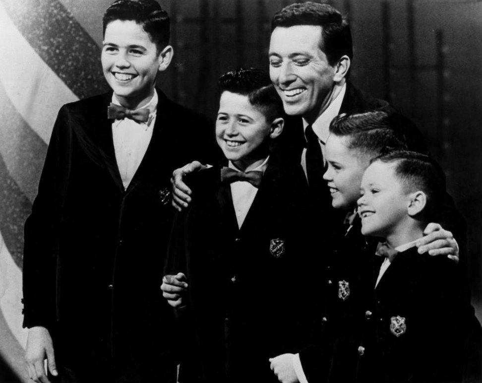 Image Source: Wikimedia Commons/Public Domain/The boys with Andy Williams in 1964 (From left: Alan, Wayne, Williams, Merrill and Jay)