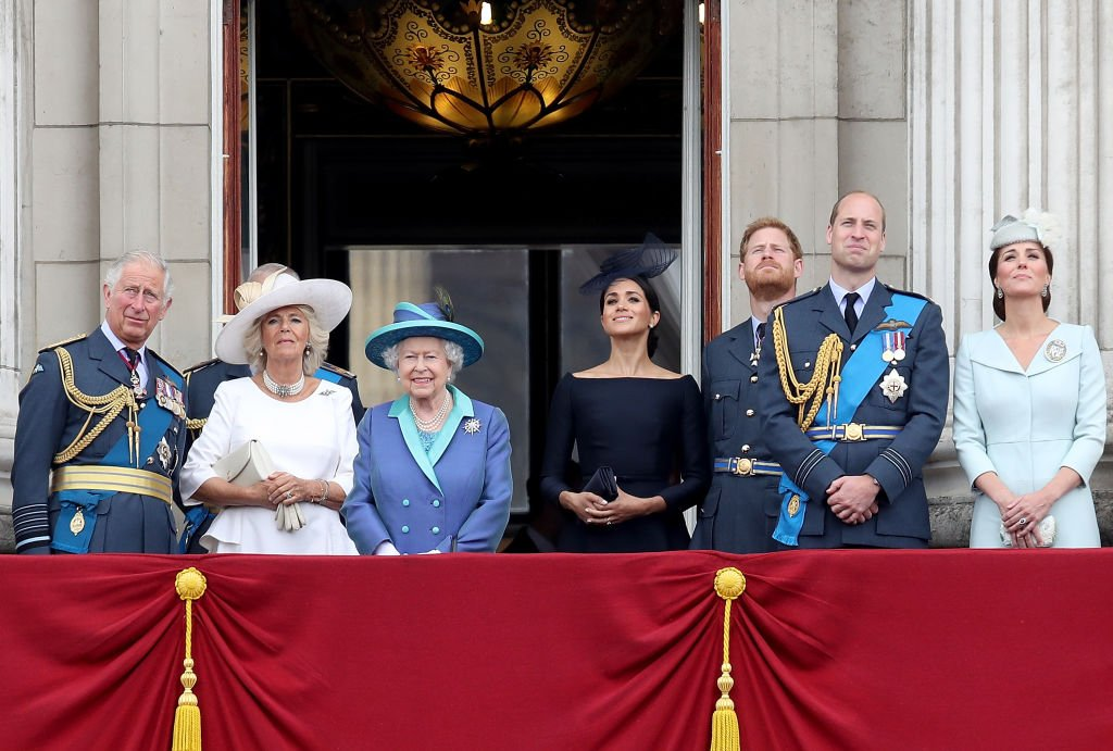 Image Credits: Getty Images / Chris Jackson   (L-R) Prince Charles, Prince of Wales, Camilla, Duchess of Cornwall, Queen Elizabeth II, Meghan, Duchess of Sussex, Prince Harry, Duke of Sussex, Prince William, Duke of Cambridge and Catherine, Duchess of Cambridge watch the RAF flypast on the balcony of Buckingham Palace, as members of the Royal Family attend events to mark the centenary of the RAF on July 10, 2018 in London, England.