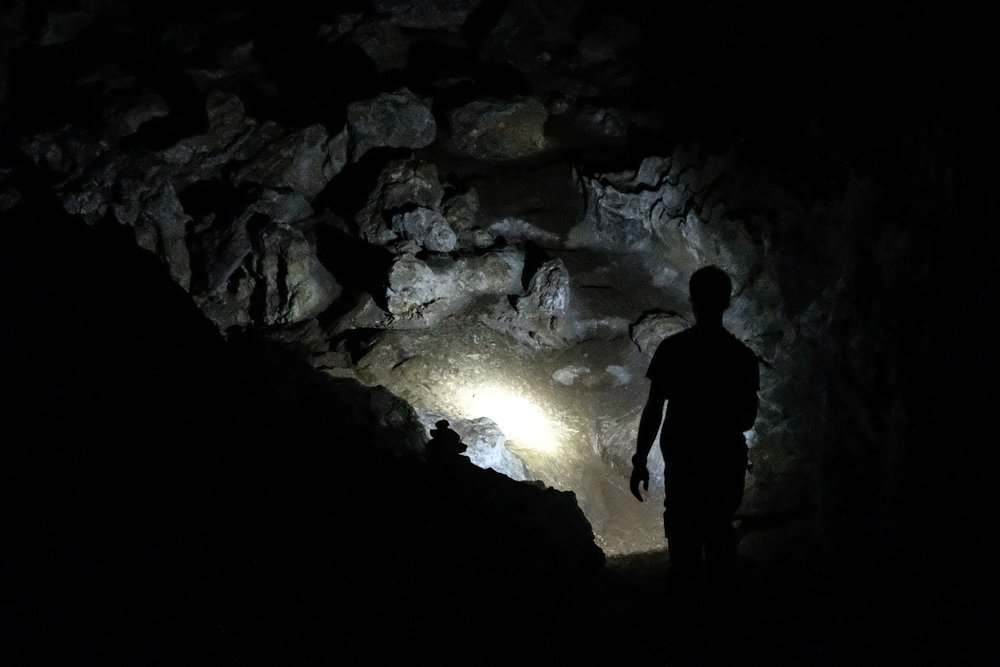 Silhouette of a man exploring a cave with a torch | Shutterstock
