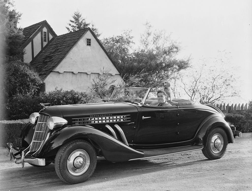 Image Source: Getty Images / Actor Errol Flynn (1909-1959), known as the king of swashbuckler films, goes for a drive in his convertible with his dog.