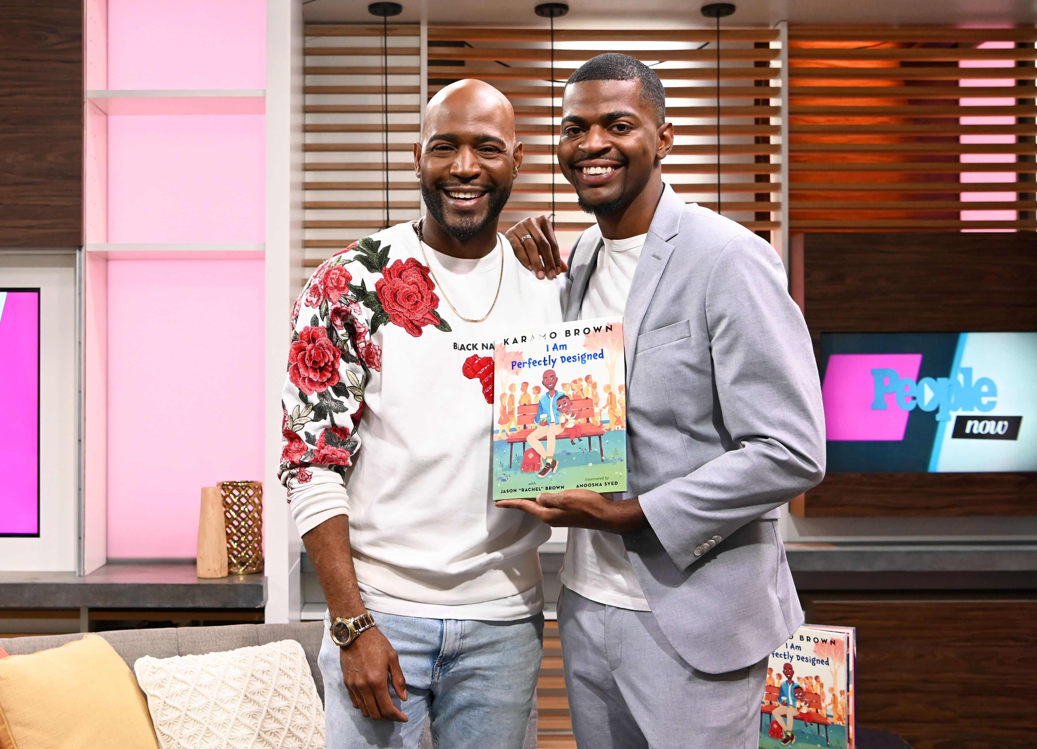 """Karamo Brown and his son Jason Brown pose with their new book """"I am Perfectly Designed"""" / Getty Images"""