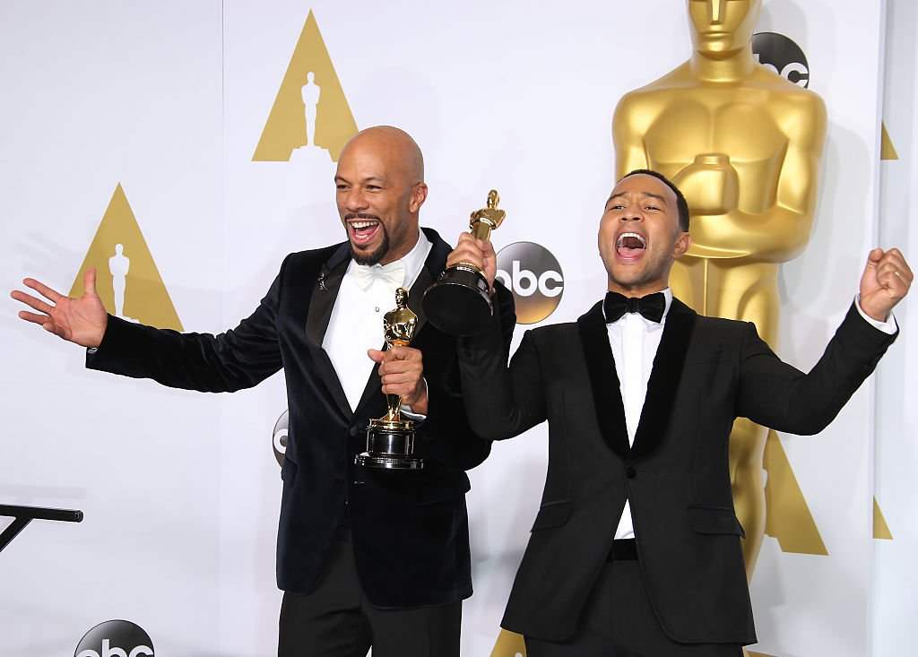 Image Credits: Getty Images / Dan MacMedan/WireImage | Common and John Legend pose in the press room with their awards for Best Original Song