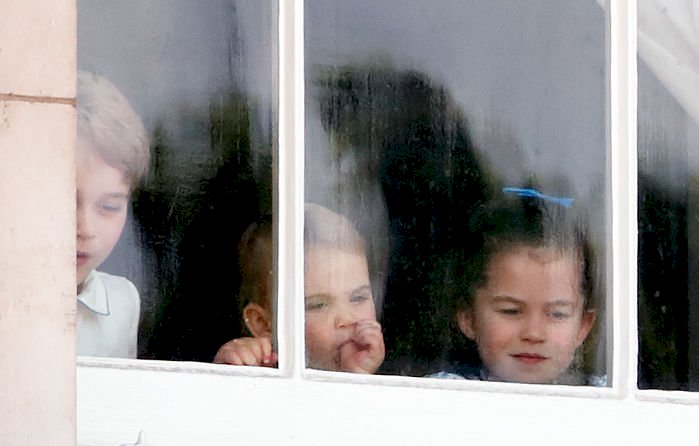 Image Credit: Getty Images / Prince George of Cambridge, Prince Louis of Cambridge (sucking his thumb) and Princess Charlotte of Cambridge look out of a window of Buckingham Palace.