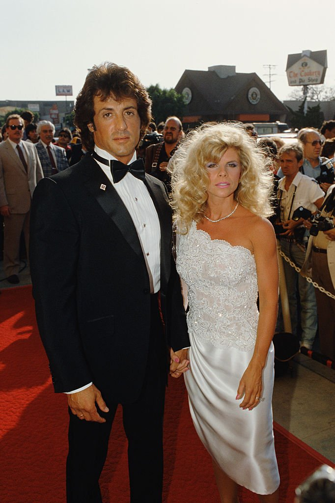 Image Credits: Getty Images / Bill Nation / Sygma | American actor, director, screenwriter and producer Sylvester Stallone and his wife Sasha Czack attend the premiere of the movie Rhinestone, directed by Bob Clark.