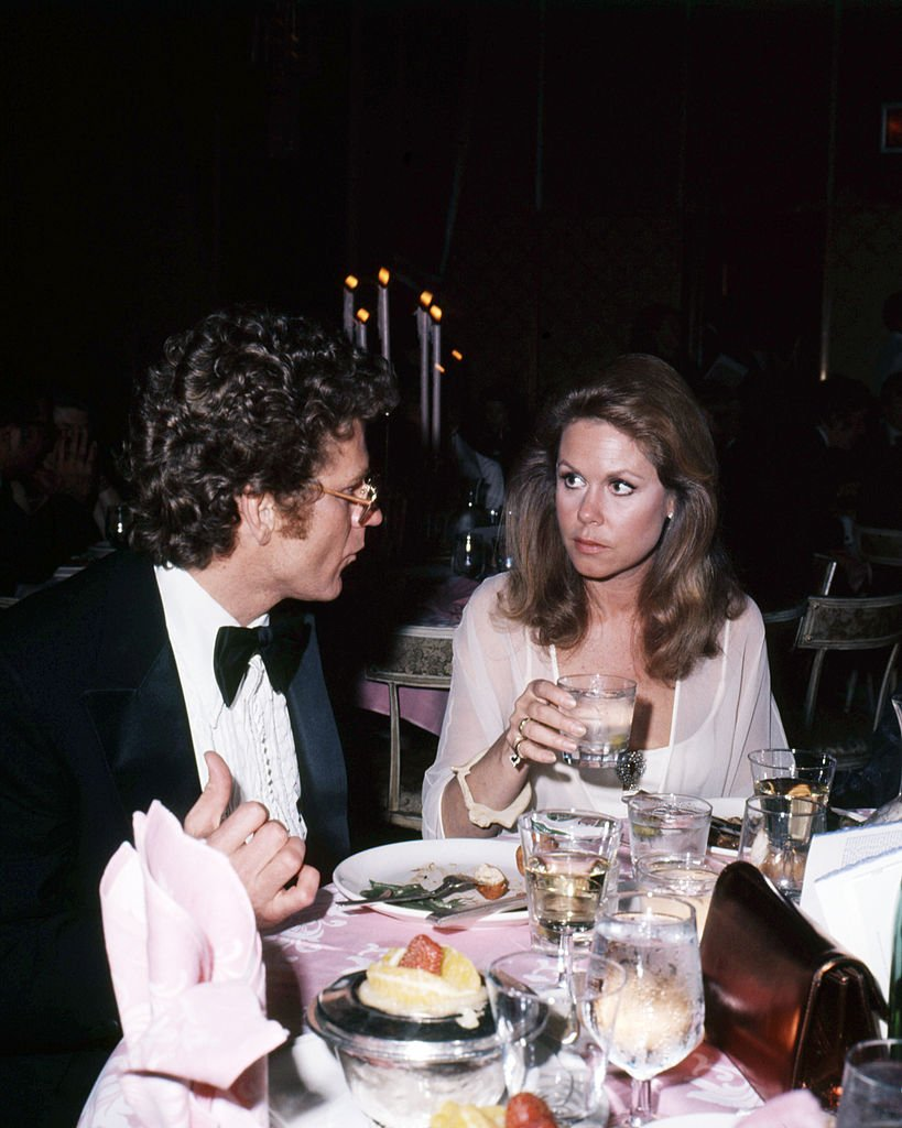 Image Credits: Getty Images / Silver Screen Collection | American actress Elizabeth Montgomery (1933 - 1995) dining with French filmmaker Andre Weinfeld, circa 1980.