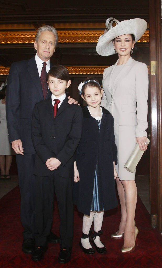 Image Credits: Getty Images / Lewis Whyld - WPA Pool | Actress Catherine Zeta Jones (R) arrives with her husband, actor Michael Douglas and their children Dylan and Carys Douglas, to attend a Royal Investiture at Buckingham Palace on February 24, 2011 in London, England.