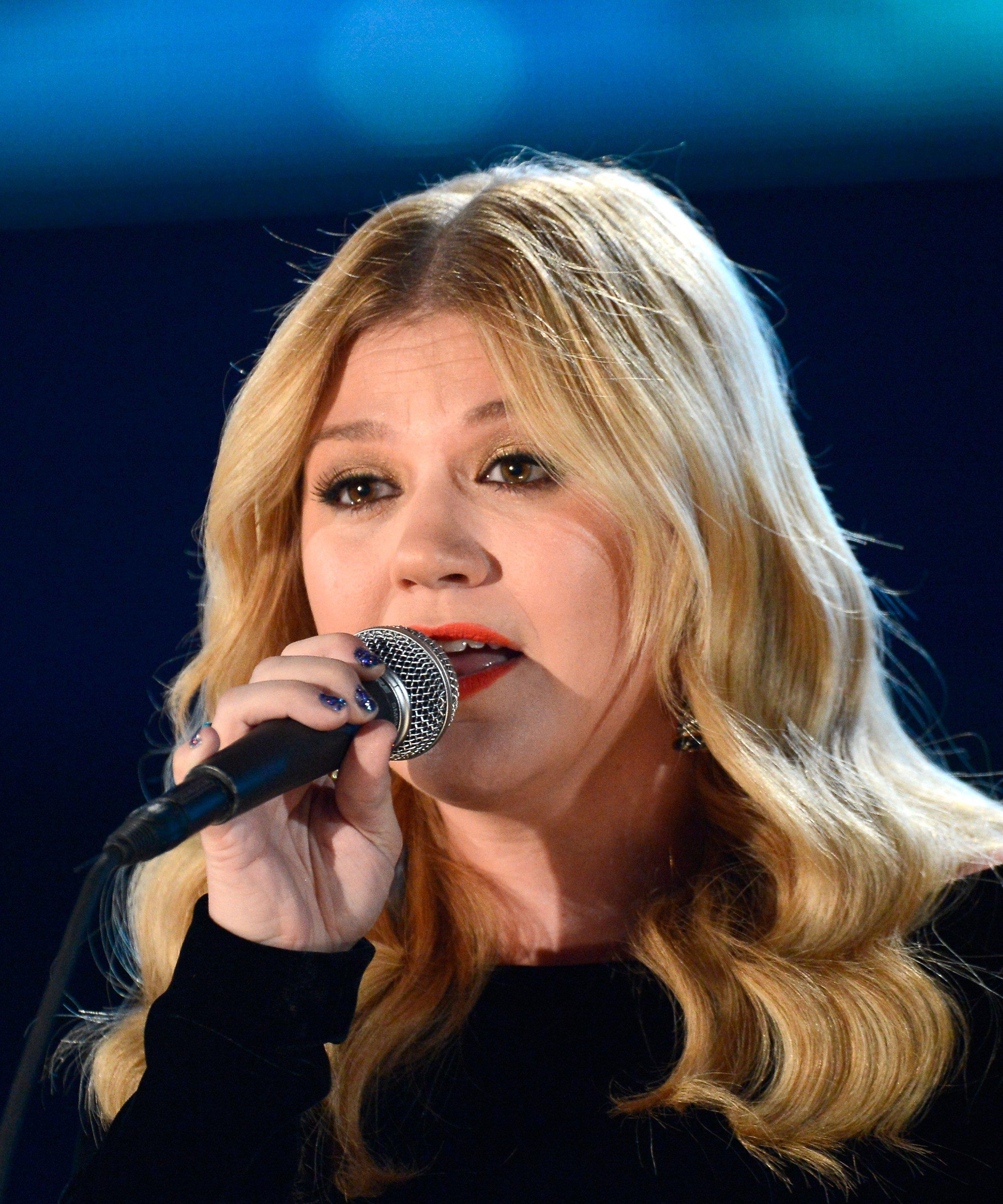 Image Source: Getty Images | Kelly singing at an event
