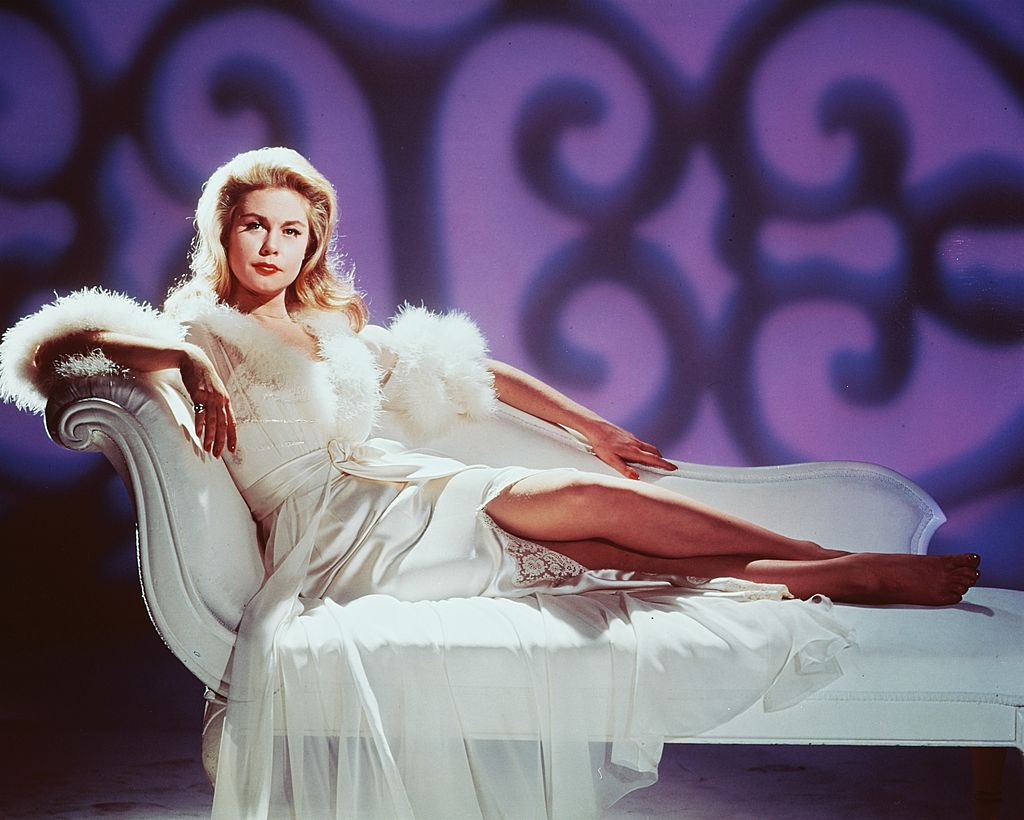 Image Credits: Getty Images / Silver Screen Collection | Elizabeth Montgomery (1933-1995), US actress, reclining on a white chaise longue, wearing a white dressing gown trimmed with white fur, circa 1965.