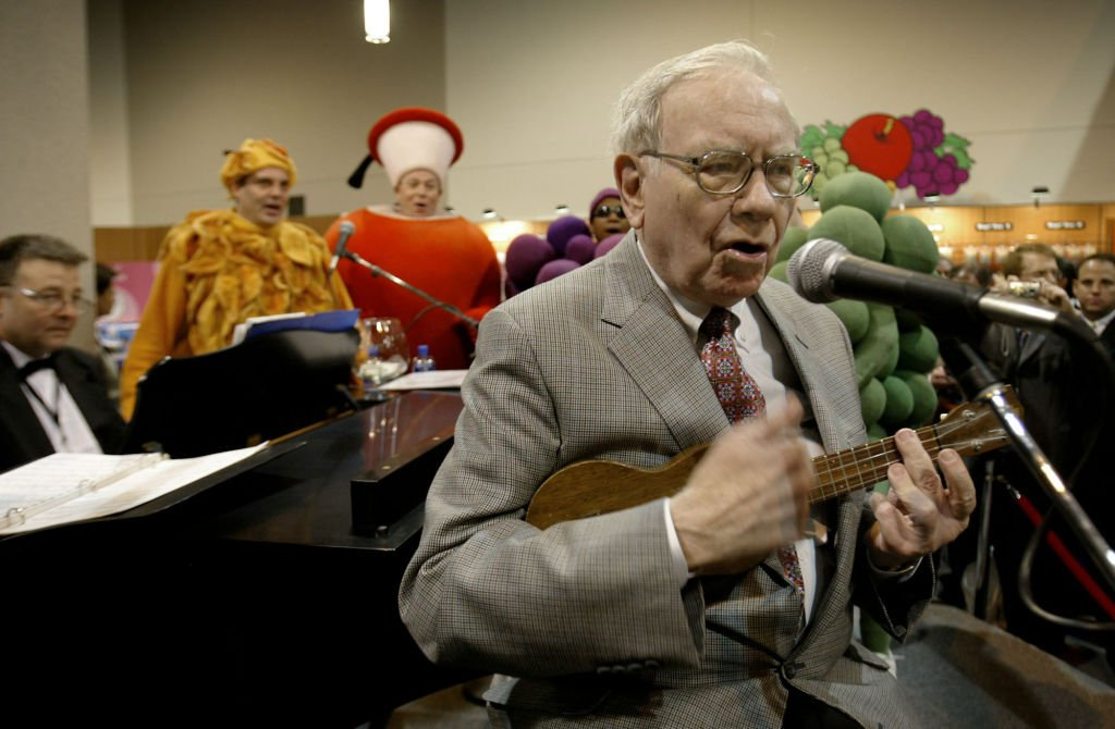 Image Credit: Getty Images / Warren Buffett, chairman of Berkshire Hathaway, plays the ukulele for a crowd of shareholders at the Fruit of the Loom booth during the Berkshire Hathaway annual meeting in Omaha, Nebraska, Saturday, April 30, 2005.