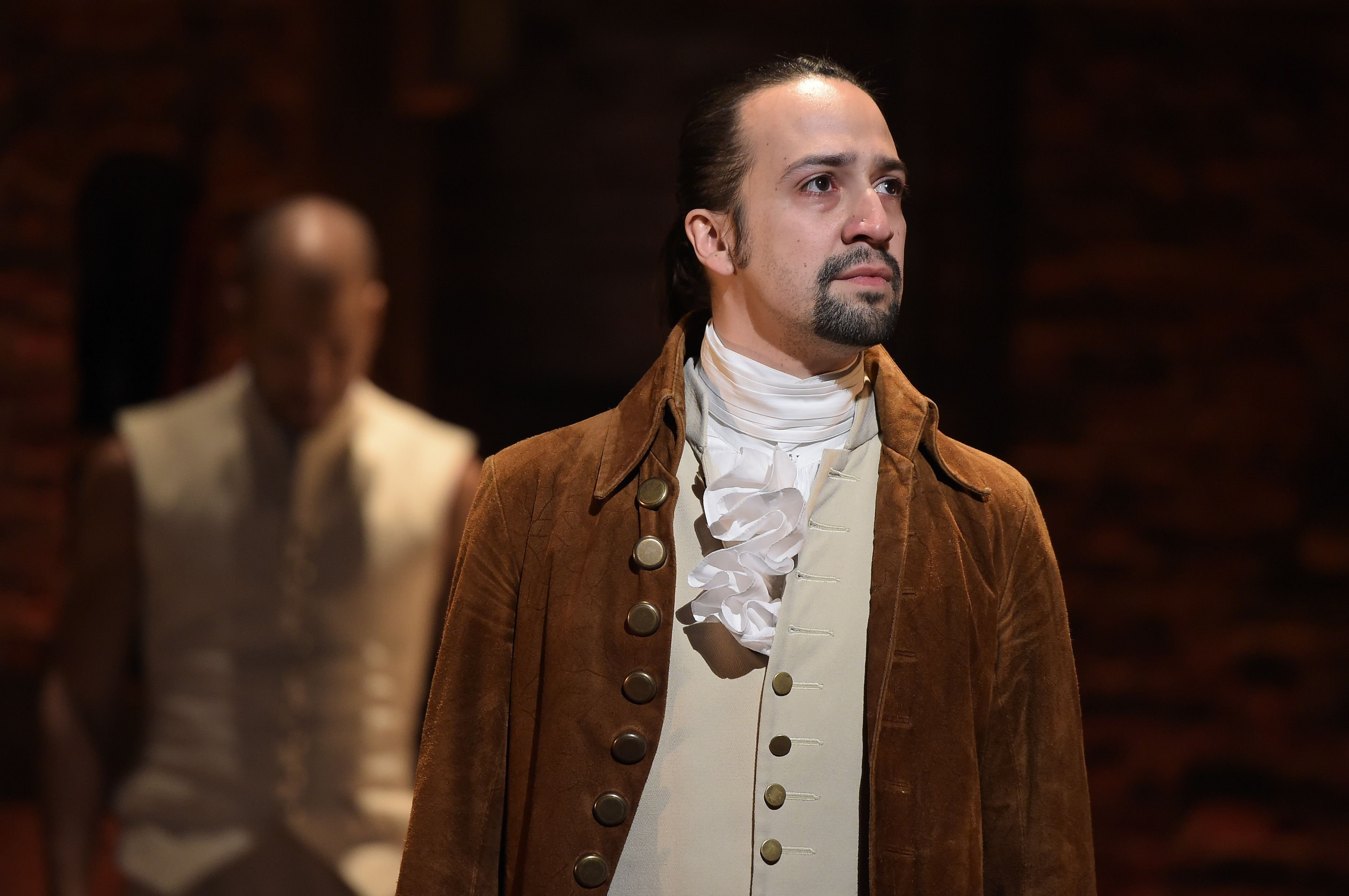 """Actor, composer Lin-Manuel Miranda is seen on stage during """"Hamilton"""" GRAMMY performance / Getty Images"""