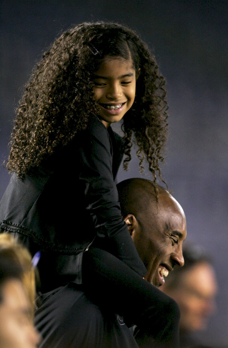 Image Credits: Getty Images / Kent C. Horner | NBA Los Angeles Laker Kobe Bryant stands on the sideline with his daughter Gianna Maria-Onore Bryant on his shoulders prior to the start of the game against the United States and China during an international firendly match at Qualcomm Stadium on April 10, 2014 in San Diego, California.