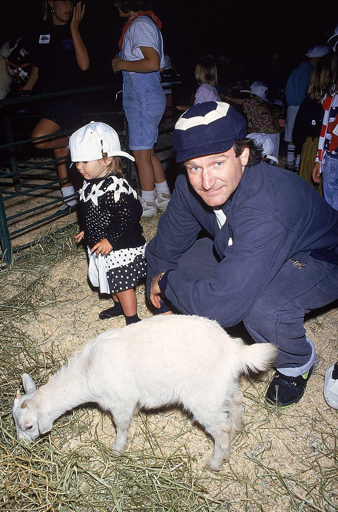 Image Credits: Getty Images / DMI / The LIFE Picture Collection | Actor Robin Williams at petting zoo charity event with daughter Zelda.