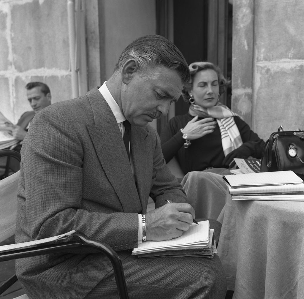 Image Credit: Getty Images / American actor Clark Gable writing next to his bride-to-be Kay Williams Spreckles sitting behind him in Venice, 1953.