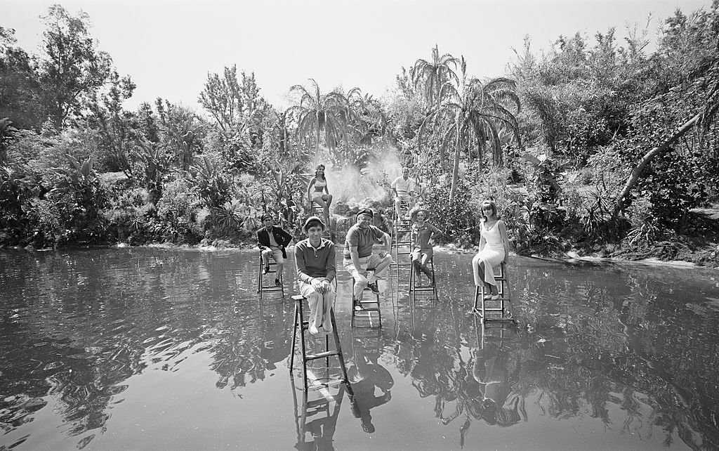 Image Source: Getty Images/CBS Photo Archive/GILLIGAN'S ISLAND. Cast posed on ladders in the lagoon. (from left) Jim Backus (as Thurston Howell III); in foreground: Bob Denver (as Gilligan); Dawn Wells (as Mary Ann Summers); Alan Hale, Jr. (as The Skipper, Jonas Grumby); Russell Johnson (as The Professor, Roy Hinkley); Natalie Schafer (as Mrs. Lovey Howell) and Tina Louise (as Ginger Grant)