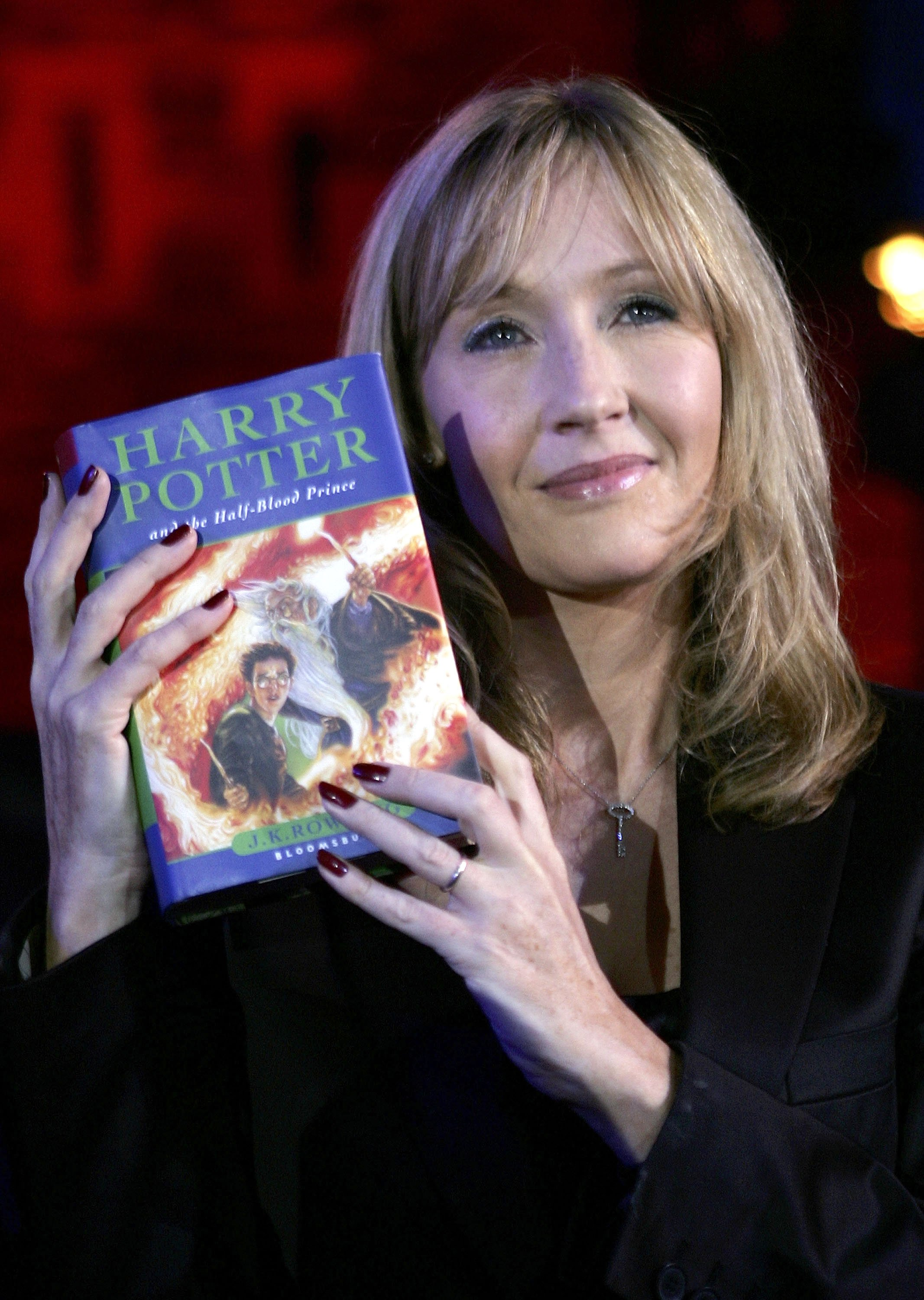 Image Credits: Getty Images | J.K. Rowling holding a copy of Harry Potter