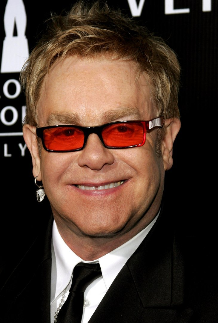 Image Credits: Getty Images / Elton John poses on the red carpet.