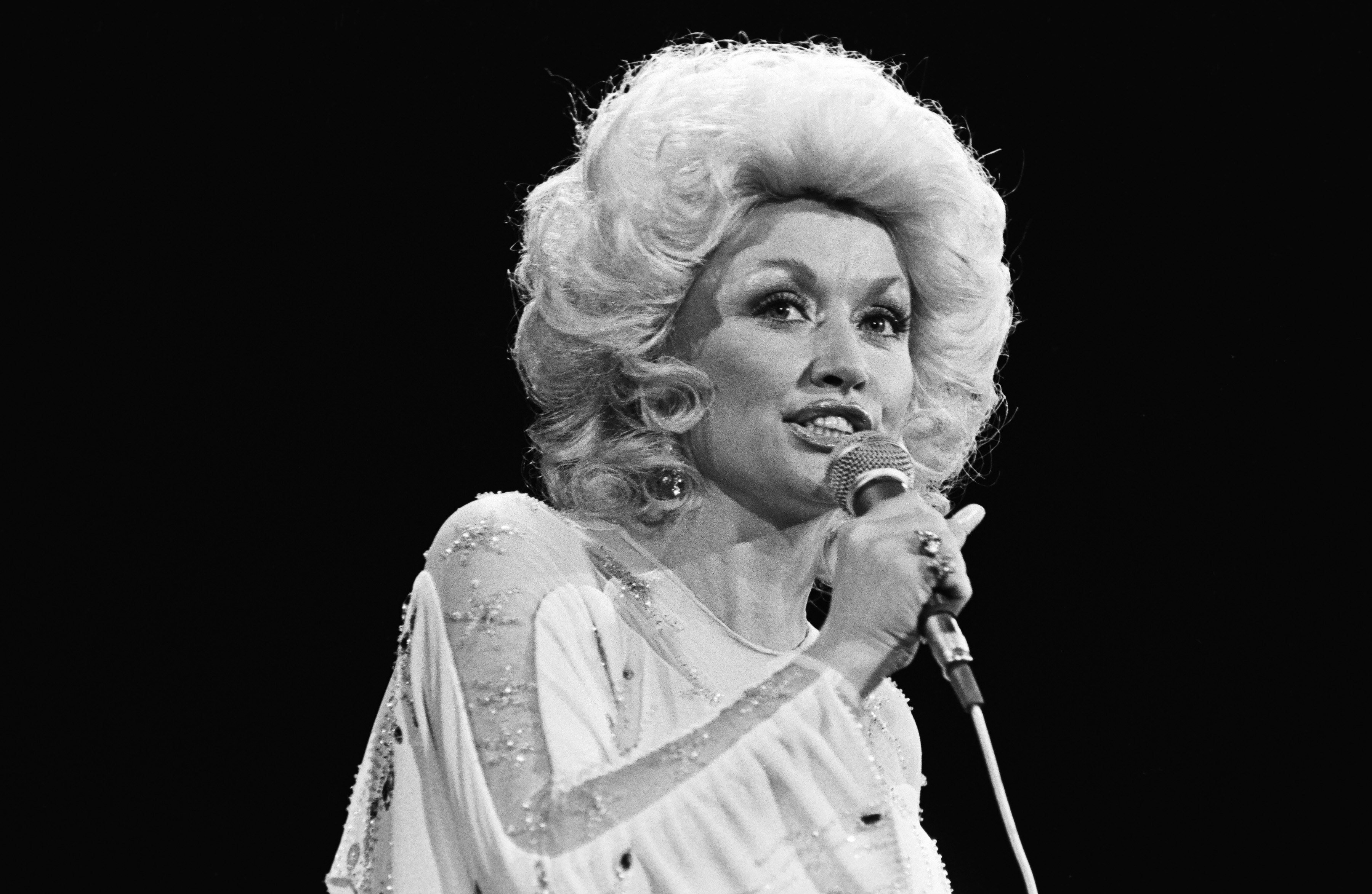 Image Credits: Getty Images / George Rose | Country singer, Dolly Parton, performs one of her many hits in this 1981 Universal City, California, live concert photo.