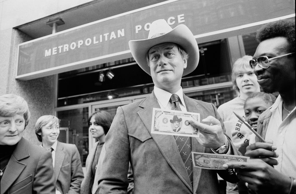 Image Credit: Getty Images / Larry Hagman, American actor and star of soap opera 'Dallas', signs a $100 bill.