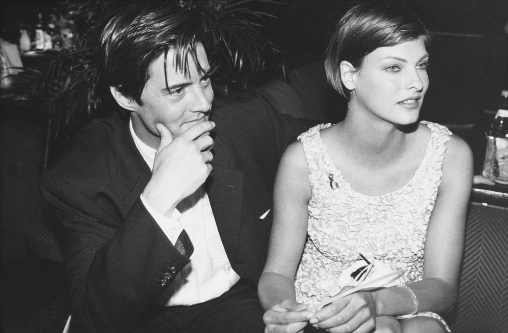 Image Source: Getty Images/Richard Blanshard | American actor Kyle MacLachlan and his girlfriend, Canadian model Linda Evangelista attend a party for the film 'Ed Wood' at the Cannes Film Festival, France, May 1995