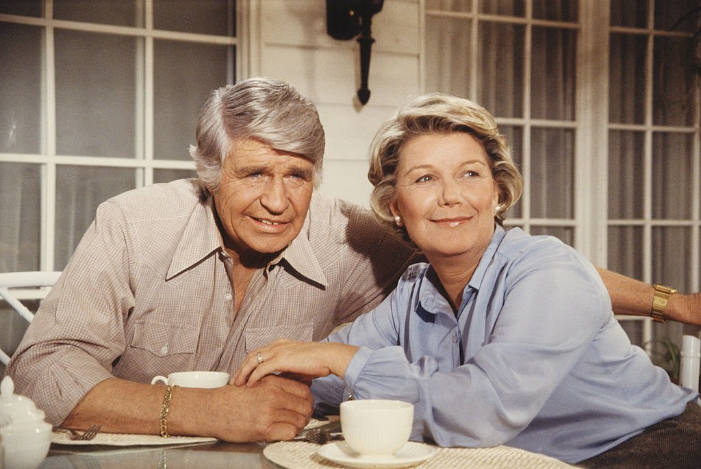 Image Credit: Getty Images / American actors Jim Davis (1909 - 1981) and Barbara Bel Geddes, as John Ross 'Jock' Ewing and Eleanor Southworth 'Miss Ellie' Ewing, sit at a table.