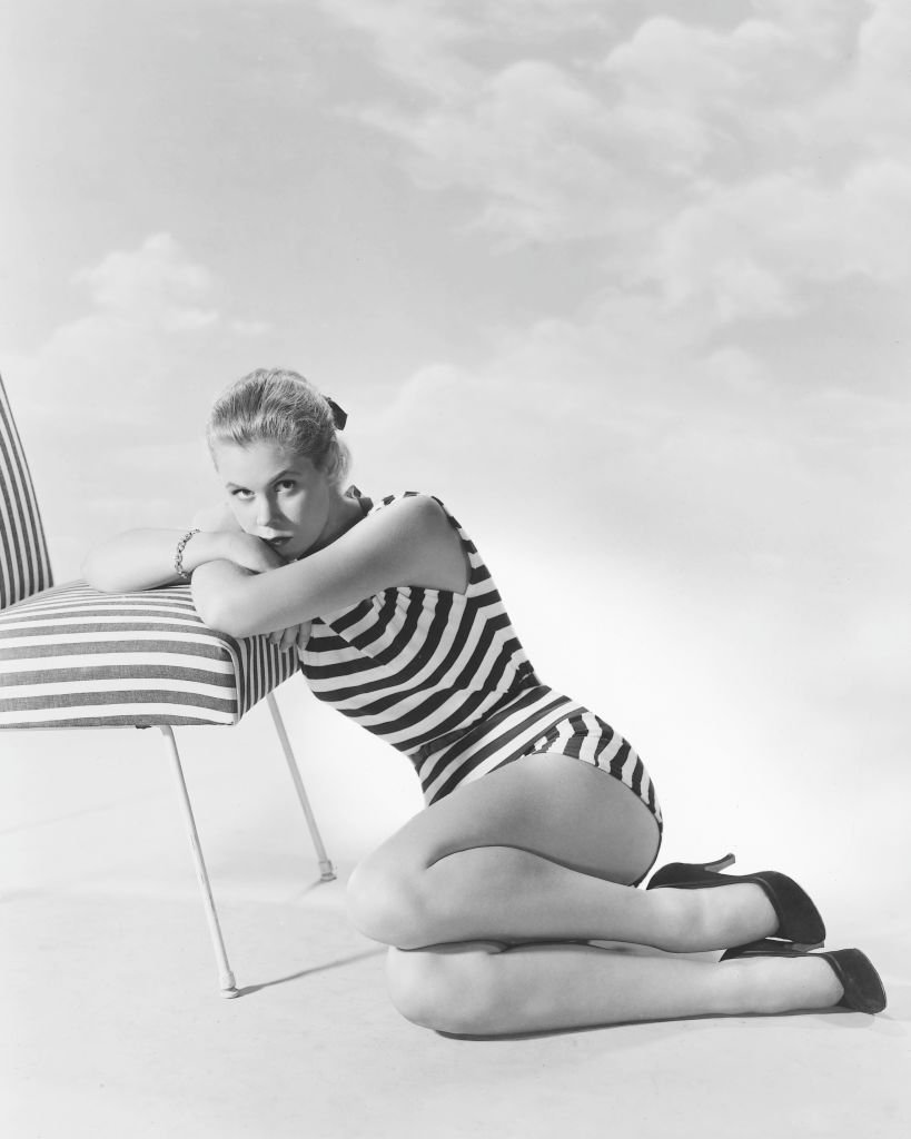Image Credits: Getty Images / Silver Screen Collection | Elizabeth Montgomery (1933-1995), US actress, wearing a striped swimsuit as she sits on the ground resting her arms and head on the seat of a striped chair in a studio portrait, against a white background, circa 1960.