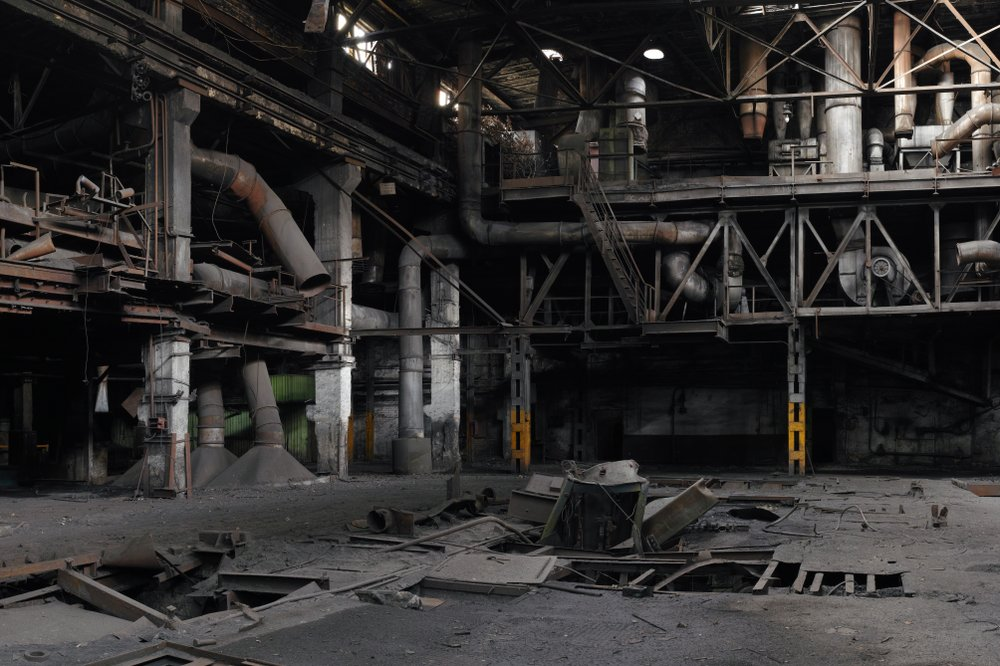 Interior of an abandoned factory with pipes and rusty metal structures, highly detailed panorama. | Shutterstock