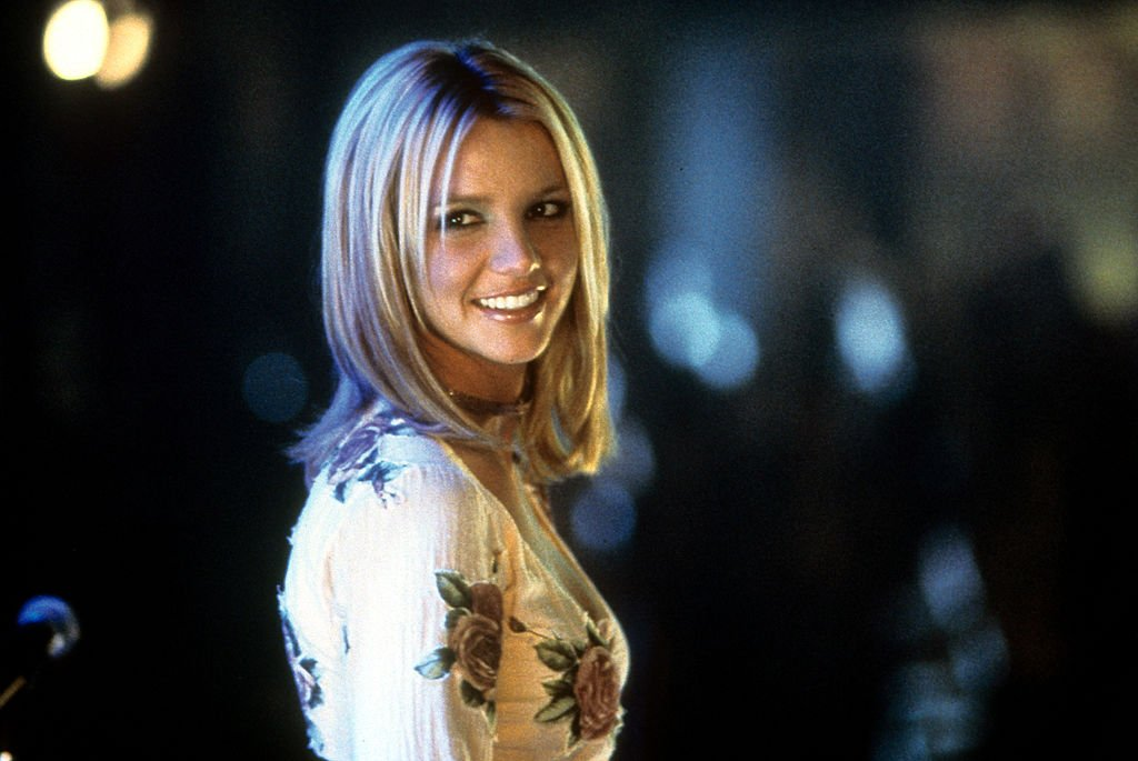 Image Credit: Getty Images / Britney Spears smiling as she looks back in a scene from the film 'Crossroads', 2002.
