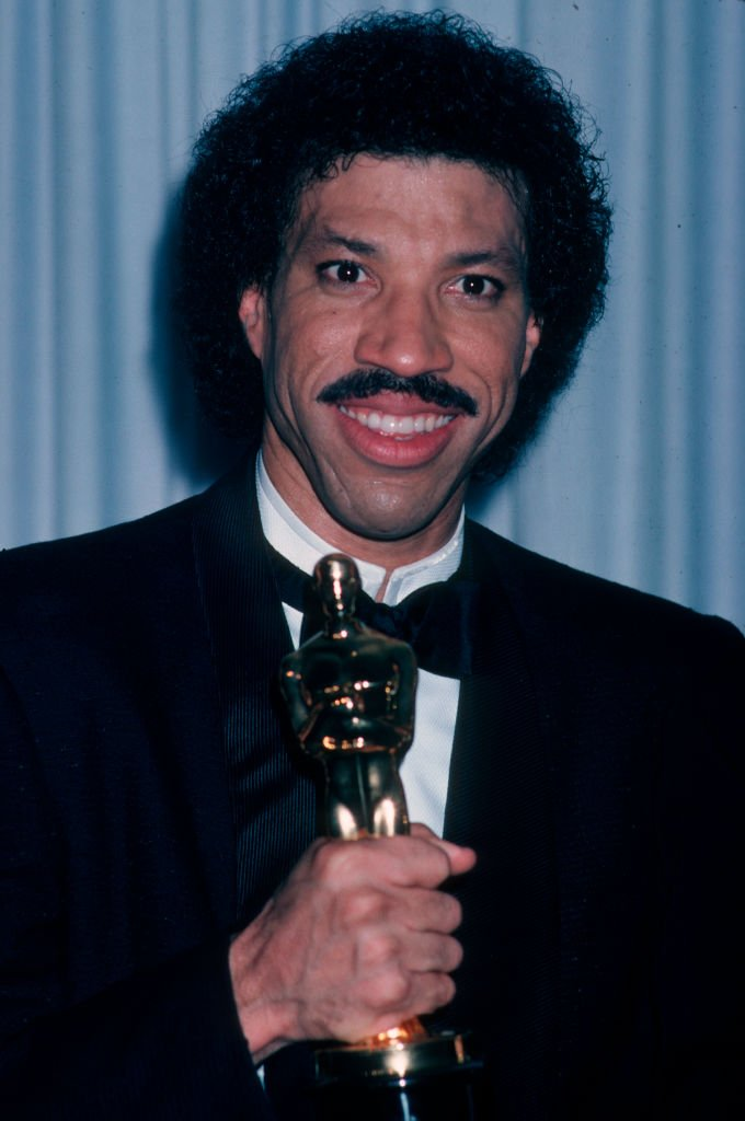 Image Credits: Getty Images / Ron Galella, Ltd./Ron Galella Collection | Lionel Richie posing with his Oscar