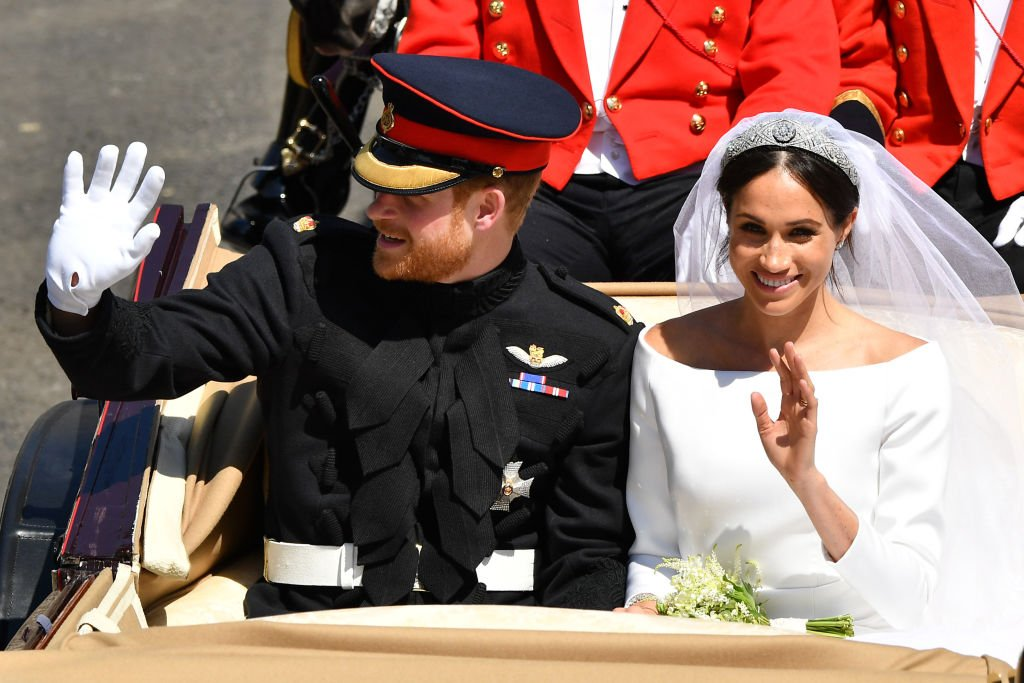 Image Credits: Getty Images / Leon Neal | Prince Harry, Duke of Sussex and Meghan, Duchess of Sussex leave Windsor Castle in the Ascot Landau carriage during a procession after getting married at St Georges Chapel on May 19, 2018 in Windsor, England.