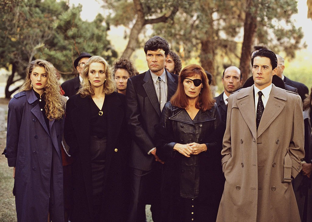 Image Credits: Getty Images / Walt Disney Television | Twin Peaks, Episode Three, Season One. FBI Special Agent Dale Cooper (Kyle MacLaughlin, right) at former homecoming queen Laura Palmer's funeral with a lineup of mourners/suspects, from left: Shelly Johnson (Madchen Amick), Norma Jennings (Peggy Lipton), Ed Hurley (Everett McGill) and Nadine Hurley (Wendy Robie).