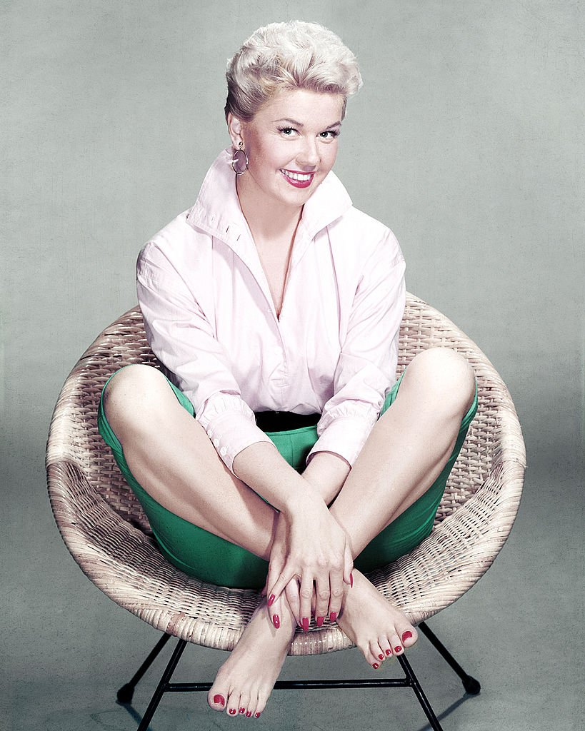 Image Credits: Getty Images / Silver Screen Collection | American actress and singer Doris Day sits cross-legged and barefoot in a rattan chair, circa 1955.