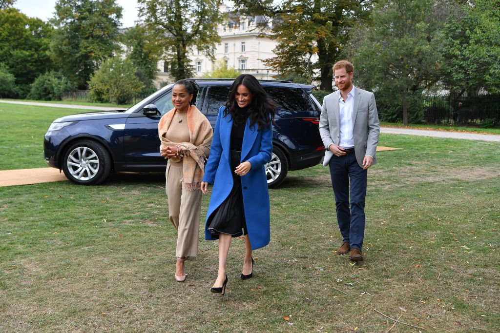 Image Credits: Getty Images / Ben Stansall - WPA Pool   Meghan, Duchess of Sussex (C) arrives with her mother Doria Ragland (L) and Prince Harry, Duke of Sussex to host an event to mark the launch of a cookbook with recipes from a group of women affected by the Grenfell Tower fire at Kensington Palace on September 20, 2018 in London, England.