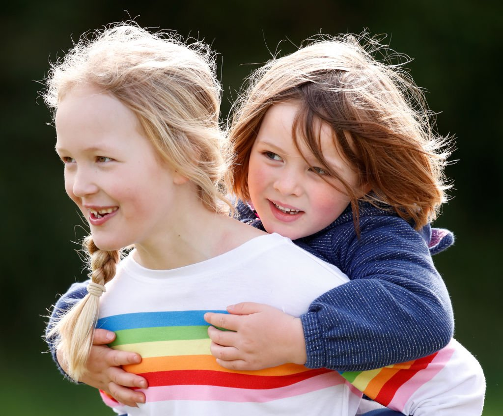 Image Credit: Getty Images / Savanah Phillips gives her cousin Mia Tindall a piggyback as they attend the Gatcombe Horse Trials on March 23, 2019 in Stroud, England.