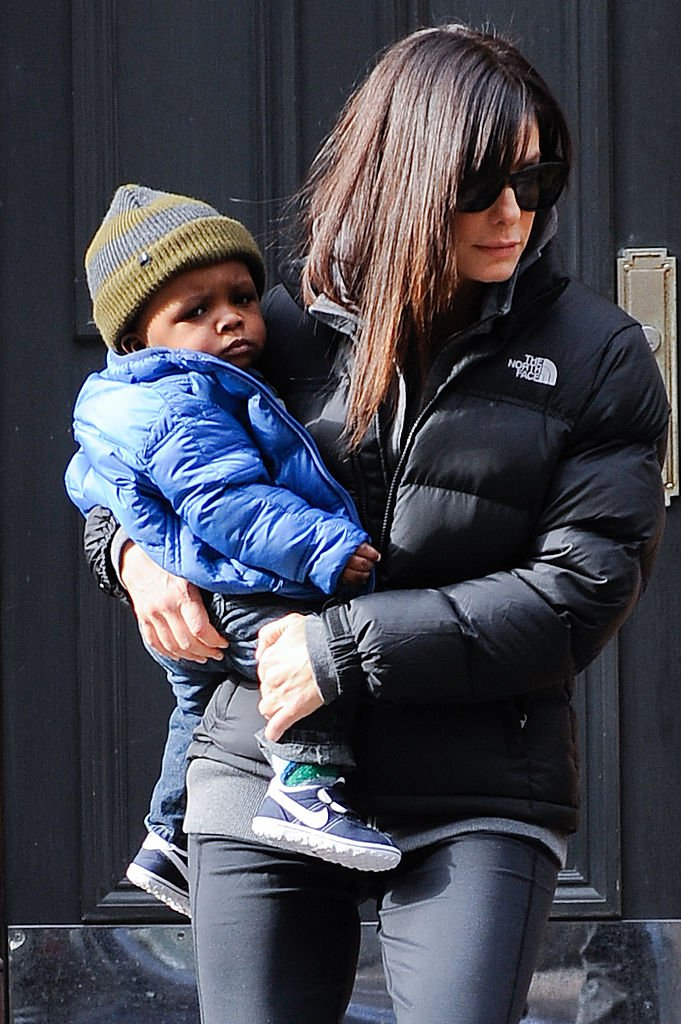 Image Credits: Getty Images / Ray Tamarra | Actress Sandra Bullock (R) and her son Louis Bullock leave their Soho home on January 20, 2011 in New York City.