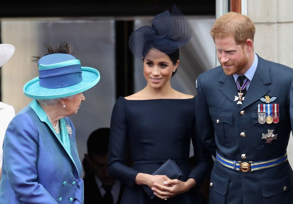 Image Credits: Getty Images / Chris Jackson | Queen Elizabeth II, Meghan, Duchess of Sussex, Prince Harry, Duke of Sussex watch the RAF flypast on the balcony of Buckingham Palace, as members of the Royal Family attend events to mark the centenary of the RAF on July 10, 2018 in London, England.