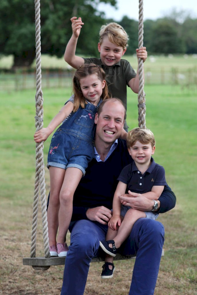 Image Credit: Getty Images / The Duke of Cambridge poses on a swing with Prince George, Princess Charlotte and Prince Louis.