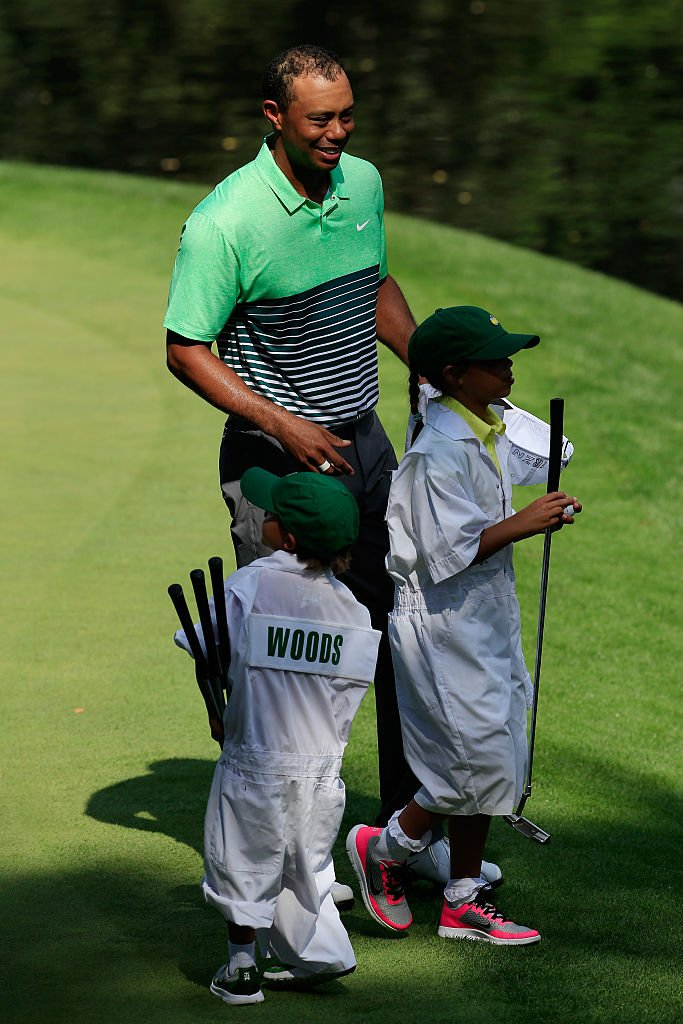 Image Credits: Getty Images / Jamie Squire | Tiger Woods of the United States waits with his son Charlie and daughter Sam during the Par 3 Contest prior to the start of the 2015 Masters Tournament at Augusta National Golf Club on April 8, 2015 in Augusta, Georgia.