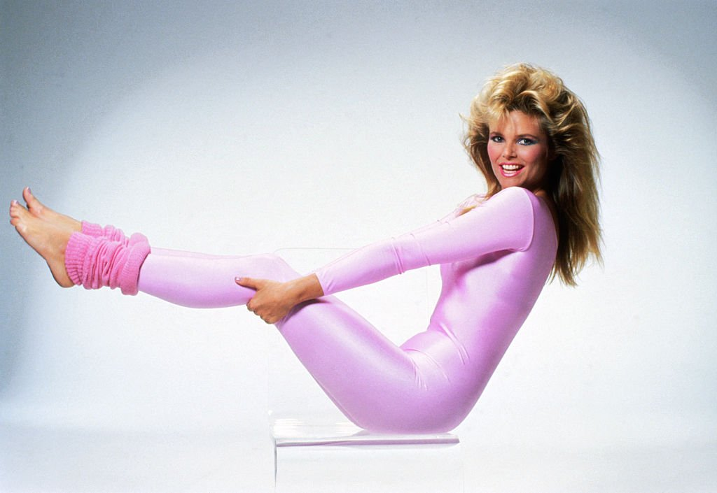 Image Credits: Getty Images / Bettmann | Christie Brinkley works out in a pink spandex unitard and leg warmers.