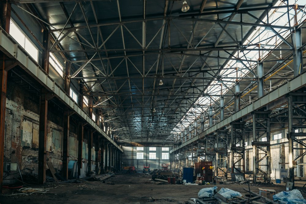 Ruined industrial hall of warehouse or hangar in process of reconstruction | Shutterstock