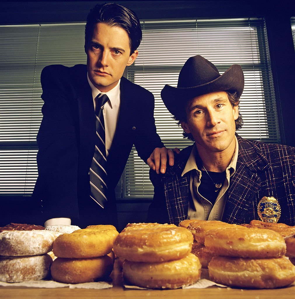 Image Credits: Getty Images / Walt Disney Television | Twin Peaks. Homecoming queen Laura Palmer is found dead, washed up on a riverbank wrapped in plastic sheeting. FBI Special Agent Dale Cooper (Kyle MacLaughlin, left) is called in to work with local Sheriff Harry S.Truman (Michael Ontkean) in the investigation of the gruesome murder in the small Northwestern town of Twin Peaks.