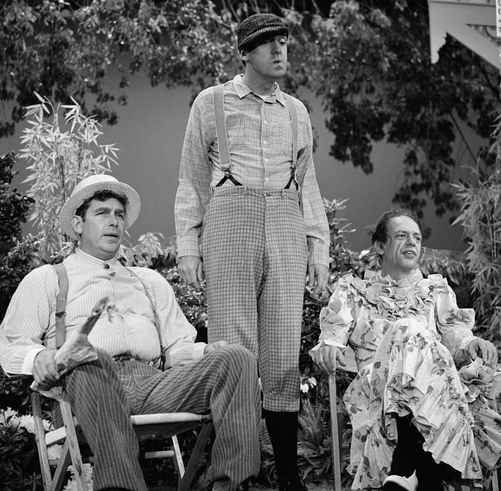 Image Source: Getty Images/CBS Photo Archive| American television actors Andy Griffith (in straw hat), Jim Nabors (dressed as a boy in a cap), and Don Knotts (in a dress) appear together in a televised skit, September 12, 1965