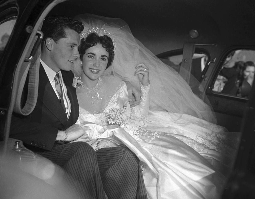"Image Credit: Getty Images / Actress Elizabeth Taylor and her groom, Conrad ""Nickie"" Hilton, Jr. off to their wedding reception at the Bel-Air Country Club."