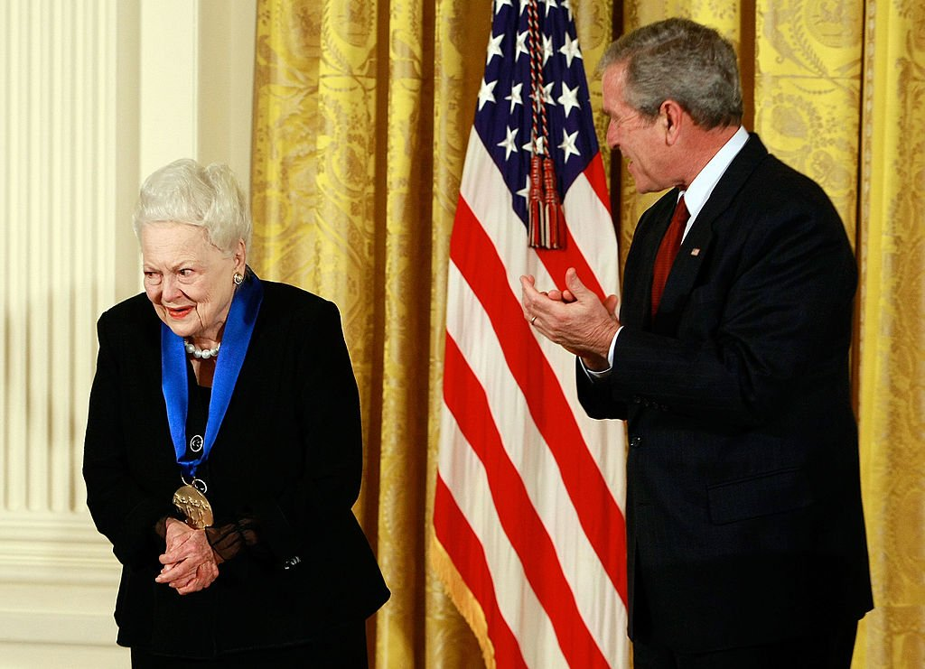 Image Credits: Getty Images / Mark Wilson | U.S. President George W. Bush congratulates actress Olivia de Havilland after presenting her with the 2008 National Medals of Arts award