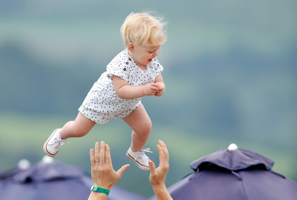 Image Credit: Getty Images / Mike Tindall throws daughter Lena Tindall into the air at Gatcombe Park on August 4, 2019 in Stroud, England.